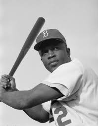 Jackie Robinson poses with a bat in 1954 during his time as a Brooklyn Dodger.