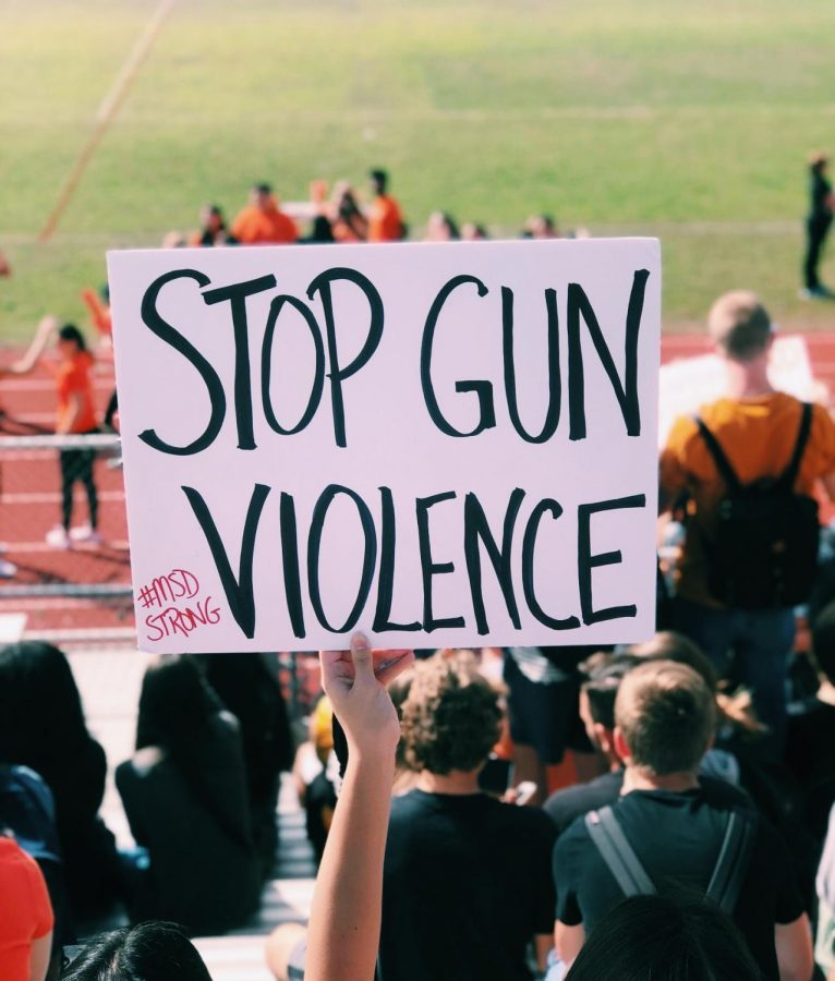 Students+gather+in+bleachers+carrying+protest+posters+to+the+Feb.+21+walkout.+
