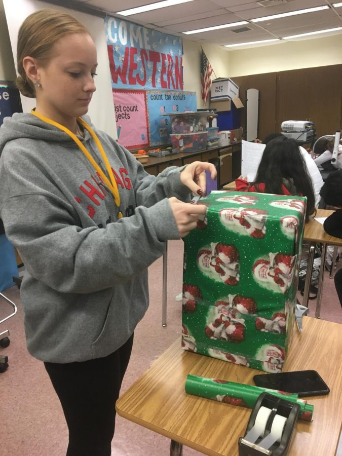 FEA president Emma Chandler wraps boxes for classrooms collecting for the toy drive.