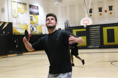 Club founder Noah Rosenthal puts his game face on as he serves the ball to a fellow club member at an April meeting.