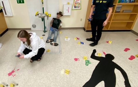 Seniors Kaitlynn Sayles and Tanner Bonneau examine the mock crime scene in Anglin's classroom on Oct. 22.