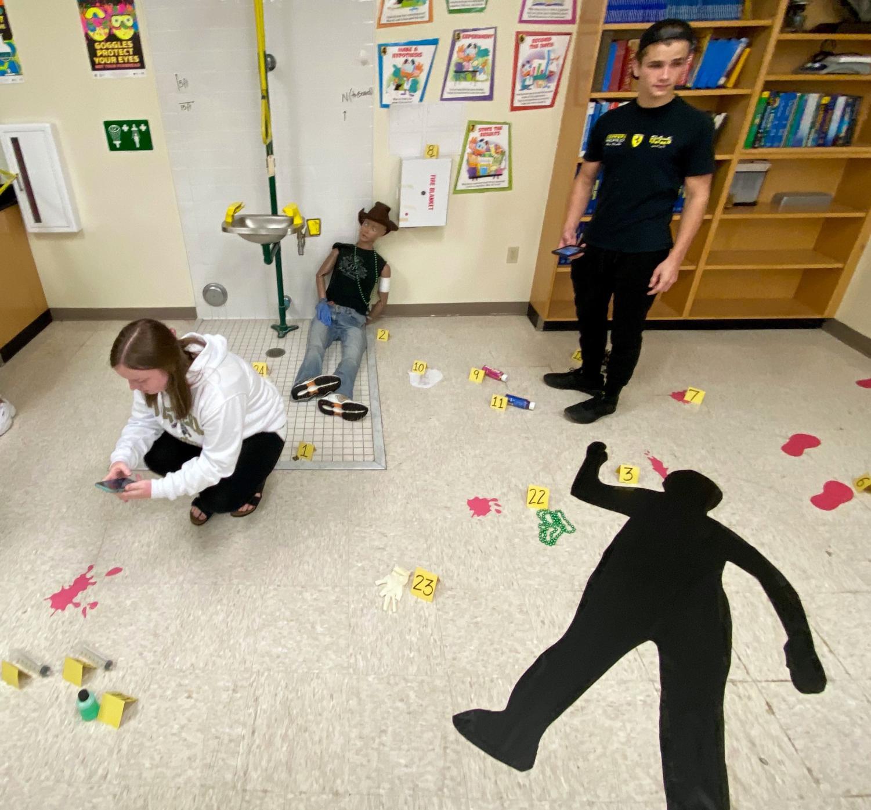 Seniors Kaitlynn Sayles and Tanner Bonneau examine the mock crime scene in Anglin's classroom on Oct. 22.