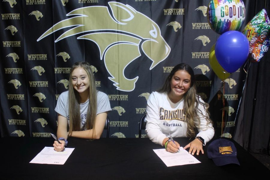 Seniors Jada Oleski and Destiny Falquez sign their Letters of Intent during signing day in the auditorium